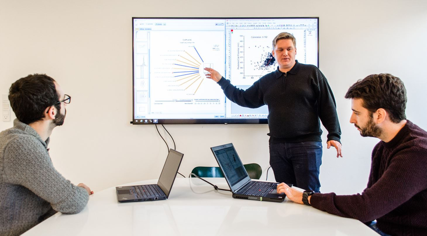 Three scientists working with Big Data on computers and a big screen